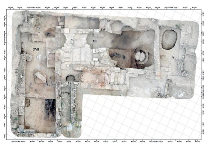 Fig. 4. Vue aérienne des installations artisanales de l'Ensemble 1: au centre l'aire de pressage avec les maies avec le contrepoids en place, sur la droite; à gauche le grand entrepôt (salle semi-enterrée) avec le bassin à 4 dolia et des éléments d'un plancher effondré (Cliché:S.Sanz).