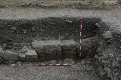 Fig.4. — Secteur 3b: vue partielle du mur méridional du trottoir depuis le nord. Les trois blocs réguliers de calcarénite au centre du cliché sont probablement les vestiges d'un support de portique (cliché L.Brassous/O.Rodríguez)