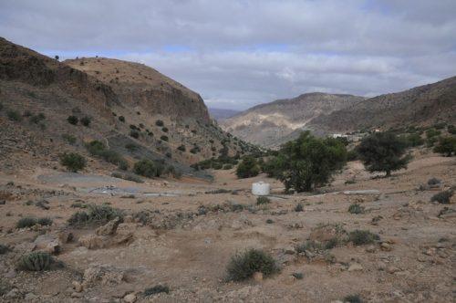 Fig. 1. — Vue d'ensemble du col surplombant le vallon de Tifigit, site de Tamggart. Au premier plan, un habitat monocellulaire médiéval (sondage 1) borde le chemin menant à la montagne d'Igîlîz (à gauche). Au fond, le village de Tifigit.©V.Héritier-Salama
